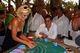 Jenny McCarthy shows cleavage in black dress during a blackjack tournament in Nassau, Bahamas